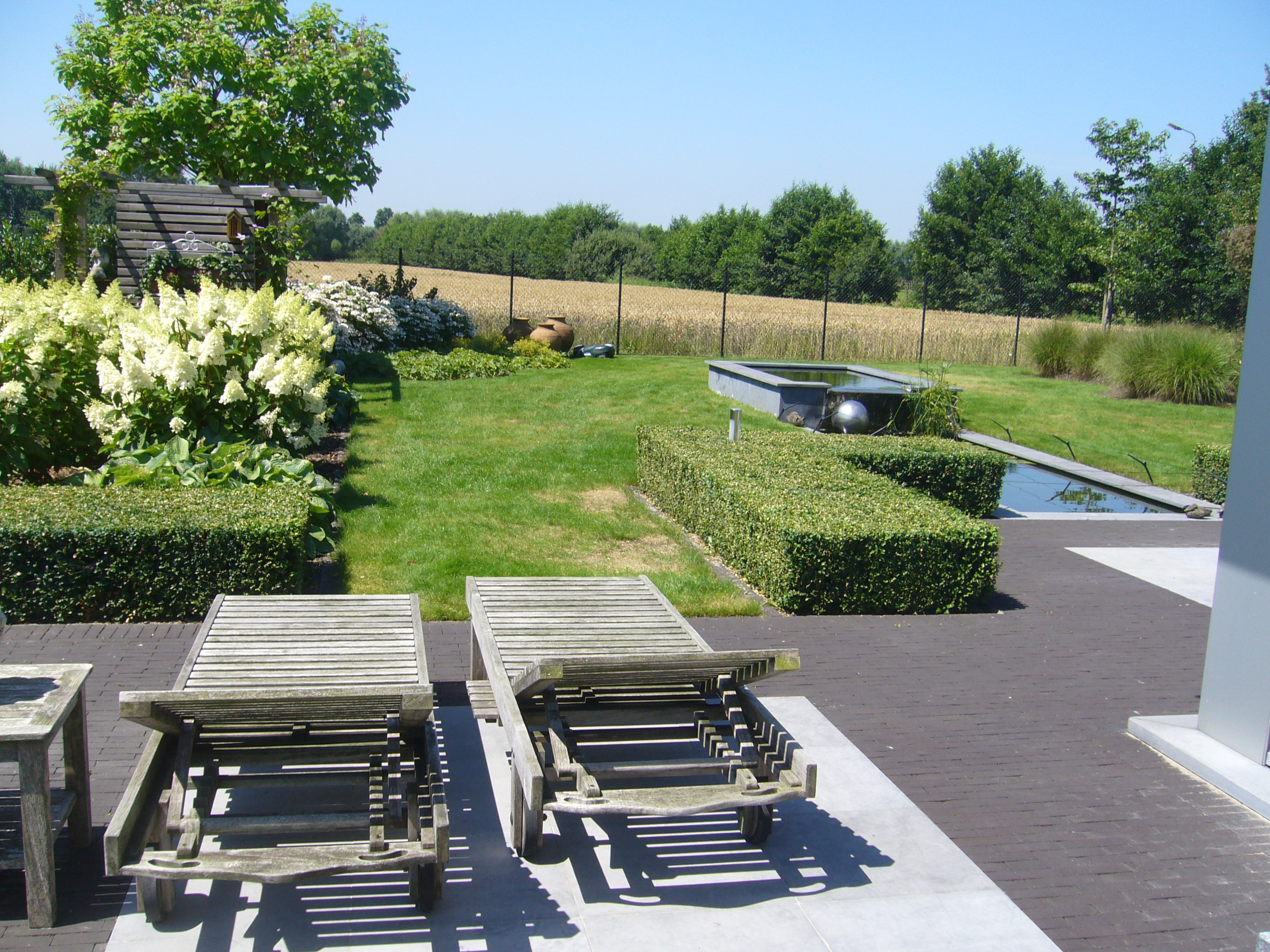 terras in blauwsteen met kleiklinker vijver landelijke tuin